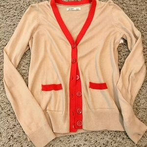 Tan cardigan with orange trim.