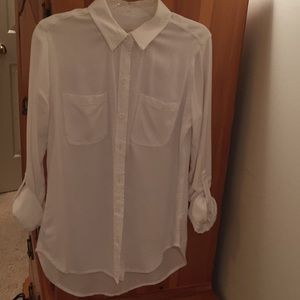 White button up shirt with rolled tan sleeves
