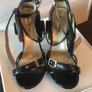 Black strappy shiny black heels with gold buckling
