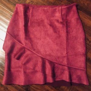 Dark pink suede mini skirt with ruffle trim.
