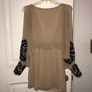 Beige dress with black ornate appliqué sleeves