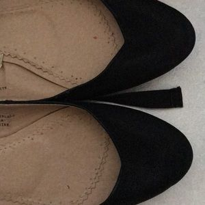 Black ballerina flats with ankle tie detail.