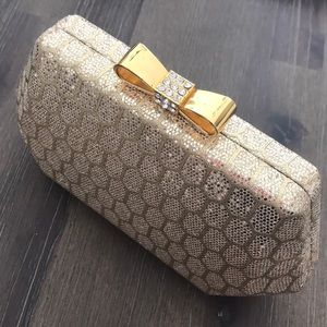 Delicate gold clutch with bow lock