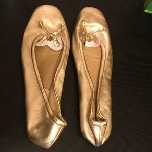 Gold flats with a bow on the top.