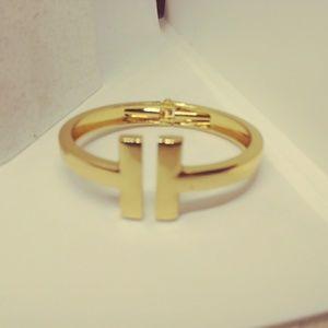 "Gold toned ""T"" bangle"