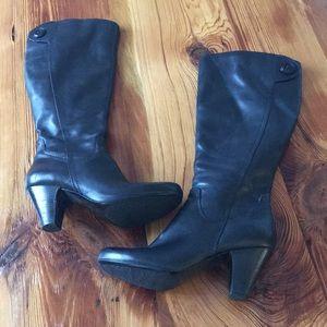 Black leather heeled knee boots.